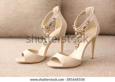 Bride's high heel shoes on sofa - stock photo