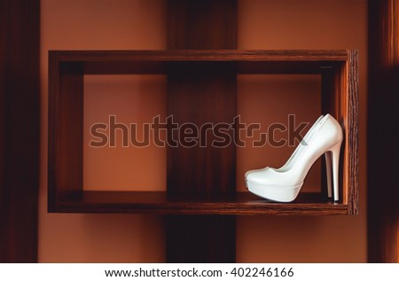 bride's white shoes on heels standing on a wooden shelf geometrically regular shape. side view - stock photo