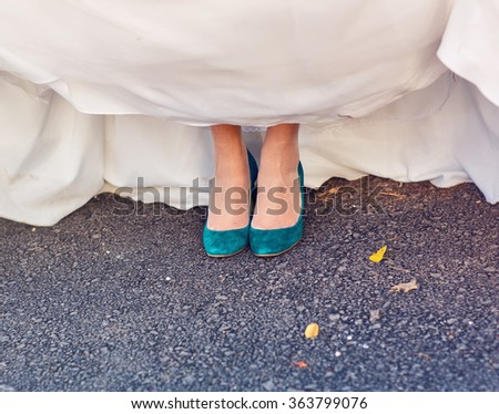 Bride  show off her turquoise shoes at wedding - stock photo