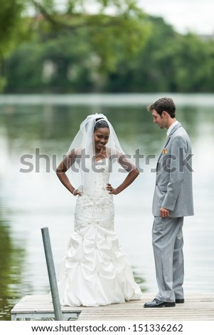 Bride showing off her dress to the groom next to a lake during wedding day - stock photo