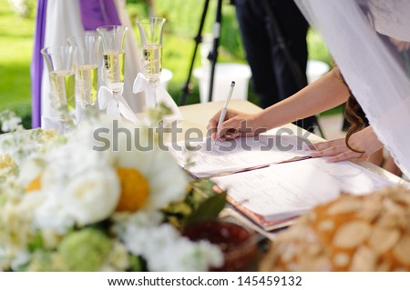 bride signing wedding certificate in park - stock photo
