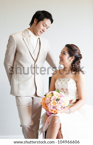 Bride sitting and Groom stand on a chair,Both are photographed in studio. - stock photo