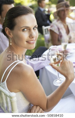 Bride sitting at wedding table, holding wineglass, smiling