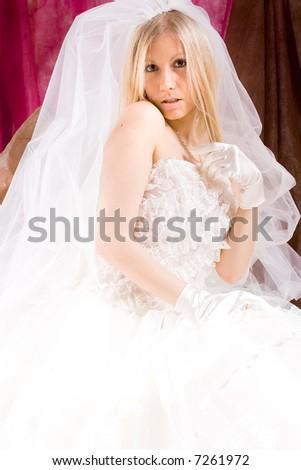 bride sitting in wedding dress, studio shot - stock photo