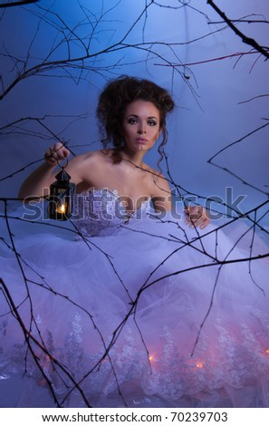 Bride sitting in wedding dress with lamp in fairytale forest at winter, like in a dream, shoot with both continuous and instant flash light made with professional makeup artist and hairdresser