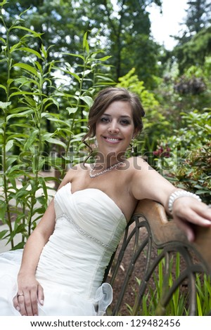 Bride sitting on a bench on wedding day - stock photo