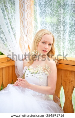 Bride sitting with a flower in the shade