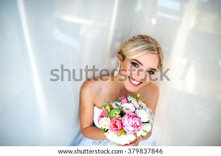 Bride smiling near a window - stock photo