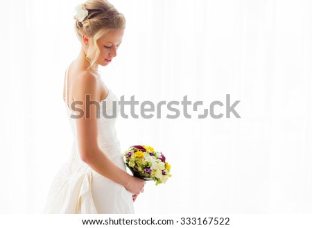Bride standing by the window in her wedding gown and flowers - stock photo