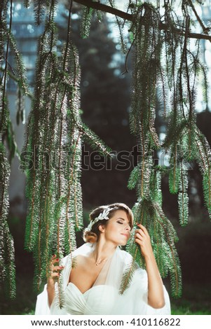 Bride standing under pine tree. Holding branches with both hands, head turned aside with closed eyes and smiling. Wearing white dress and veil on shoulders. Outdoor, waist up, profile