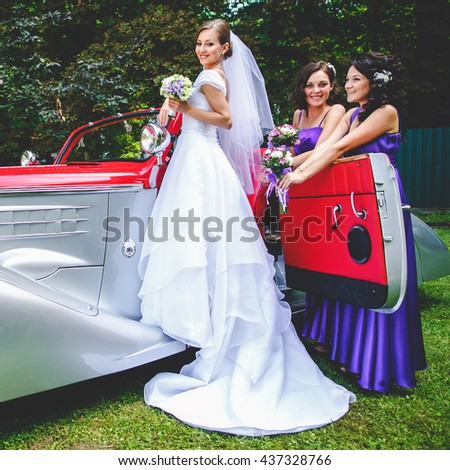 Bride stands on a doorstep of an old vintage car while bridesmaids wait behind her - stock photo
