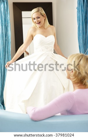 Bride trying on wedding dress with sales assistant - stock photo