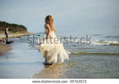 Bride walking along sea coast in the wedding dress - stock photo