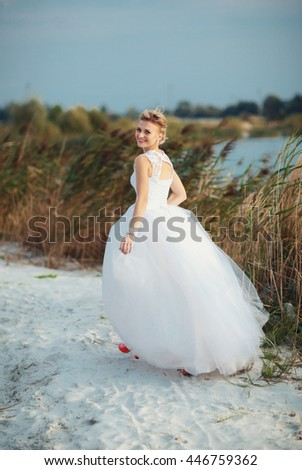 Bride walks next to the lake in the wedding day - stock photo
