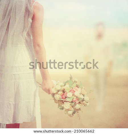Bride with a bouquet on the beach. Vintage look. - stock photo