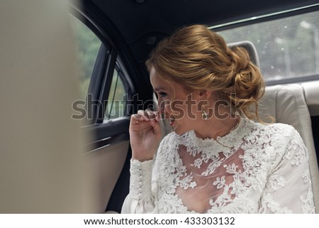 Bride with blonde hair smiles looking through the window while she sits in the car - stock photo