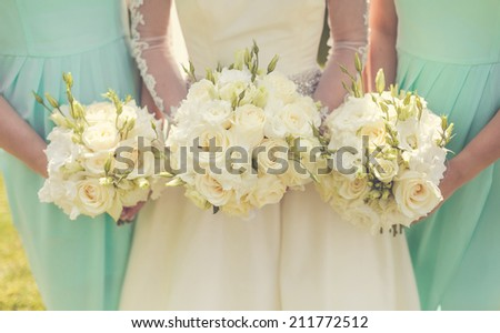 Bride with bridesmaids holding wedding bouquets - stock photo
