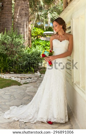 Bride with flowers stays near white wall. - stock photo
