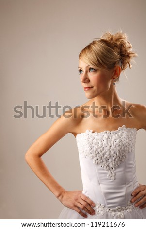 Bride with her hands on waist is looking away