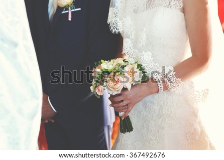 Bride with luxury bouquet of roses on her wedding ceremony near the elegant groom in the hall of the church or marriage registration office. - stock photo