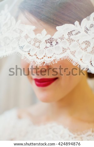 bride with red lips under the veil