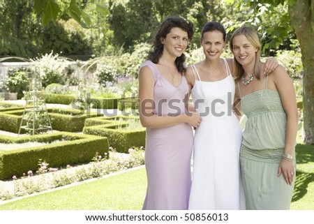 Bride with two women in garden, embracing, smiling, portrait