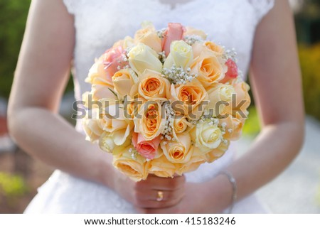 Bride with wedding rose bouquet outdoors