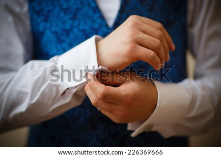 Bridegroom preparing for the wedding, straightens his shirt sleeves - stock photo