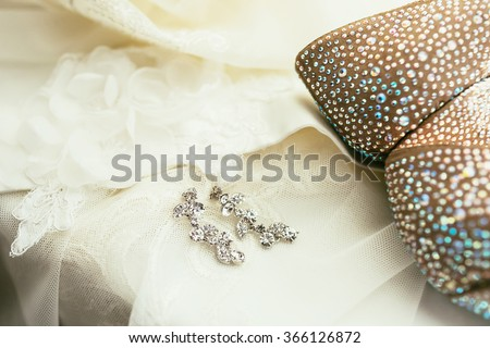 brides ear-rings on wedding dress background - stock photo