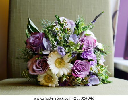 Brides purple bouquet of flowers on wedding day - stock photo