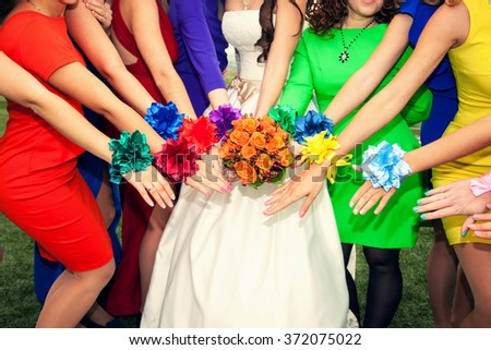 brides with an orange bouquet and bridesmaids in colorful dresses with bracelets on hands - stock photo