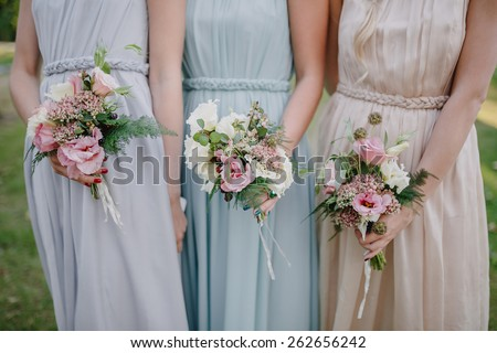 bridesmaid dresses in pastel are holding bouquets in a rustic style - stock photo