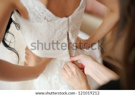 bridesmaid helping to lace up bride's wedding dress - stock photo