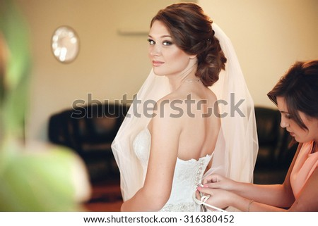 Bridesmaid helps the bride to wear a beautiful dress - stock photo