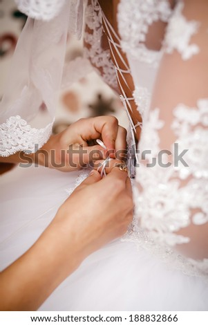 Bridesmaid helps to bride to put on a wedding dress. - stock photo