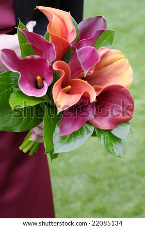 Bridesmaid holding a colorful bouquet at wedding - stock photo