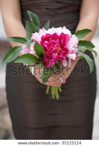 Bridesmaid holding colorful wedding bouquet against dress - stock photo