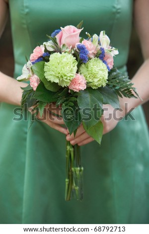 Bridesmaid holding colorful wedding bouquet against green dress - stock photo