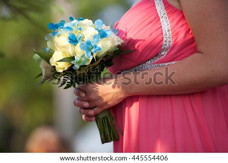 Bridesmaid holding her bouquet at the wedding. - stock photo