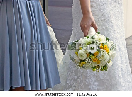 Bridesmaid holding the brides train with bouquet of flowers
