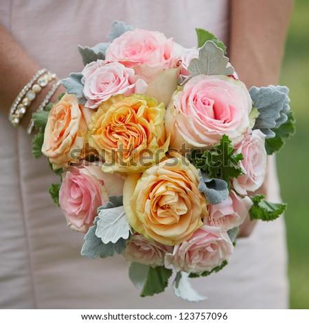 Bridesmaid holding wedding bouquet of roses - stock photo