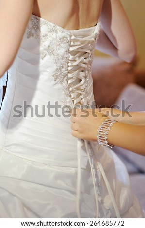 Bridesmaid is helping the bride to dress. - stock photo