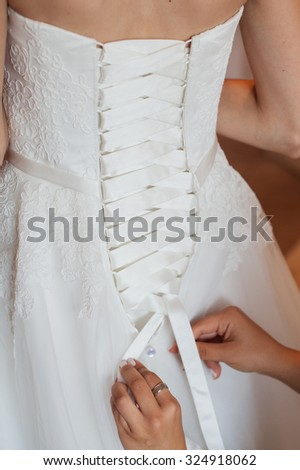 Bridesmaid is helping the bride to dress.