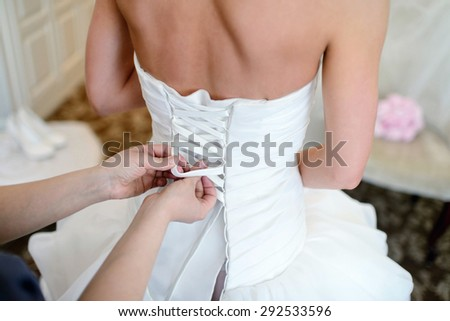 Bridesmaid is lacing white wedding dress for beautiful bride. Beauty model girl in bridal gown for marriage. Female portrait. Woman with curly hair. Cute lady indoors