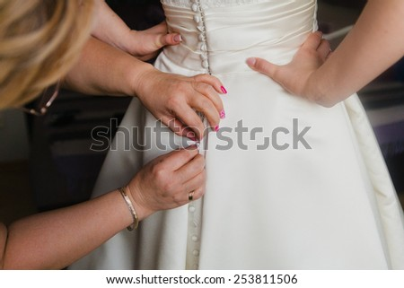 Bridesmaid with buttons of the bride's dress - stock photo