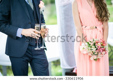 Bridesmaids and friend of the groom at a wedding ceremony in a suit and festive dress - stock photo