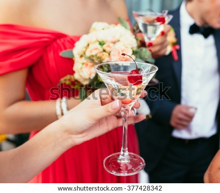 bridesmaids Drinking martini cocktails with red cherry on the wedding