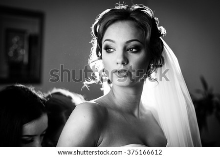 Bridesmaids helping gorgeous bride prepare for wedding closeup b&w - stock photo