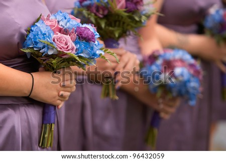 Bridesmaids holding colorful bouquets at wedding ceremony - stock photo
