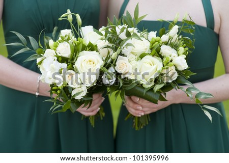 bridesmaids in green dresses holding bouquet of roses at a wedding - stock photo